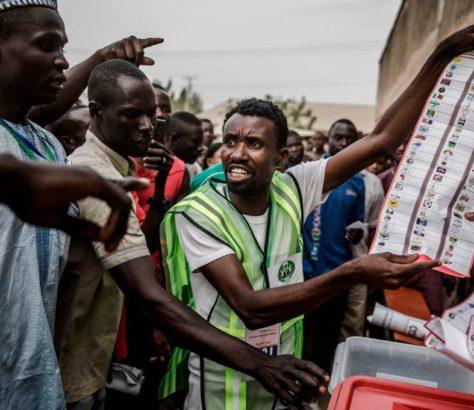 Black men holding a voter's registration form